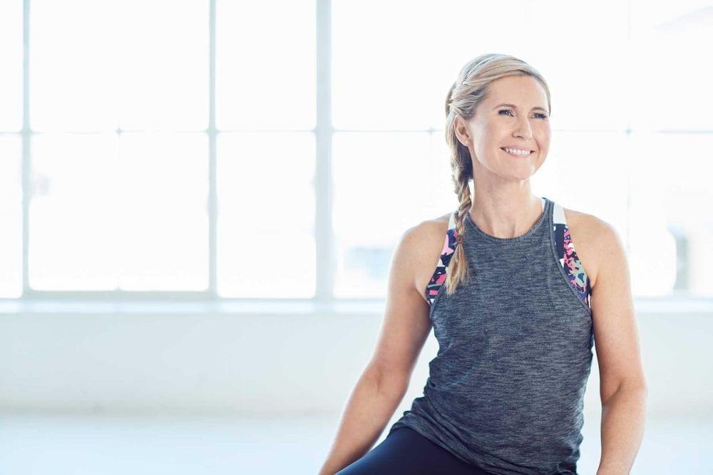 Rachel Grunwell smiling while doing Yoga